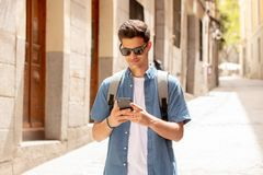 Happy young student male texting on his smart phone in modern city. Young happy student man in jeans denim clothes wearing sunglasses texting on his smart mobile Royalty Free Stock Photos