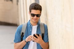 Happy young student male texting on his smart phone in modern city. Young happy student man in jeans denim clothes wearing sunglasses texting on his smart mobile Stock Image