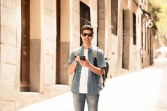 Happy young student male texting on his smart phone in modern city. Young happy student man in jeans denim clothes wearing sunglasses texting on his smart mobile Royalty Free Stock Image