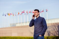 Happy young student man accepted for foreign exchange. Program. Foreign young student man speaking on mobile phone telling good news to his family royalty free stock photography