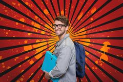 Happy young student man holding a folder against red, black and orange splattered background. Digital composite of Happy young student man holding a folder Royalty Free Stock Photos