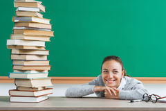 Happy young student with pile of books. Royalty Free Stock Images