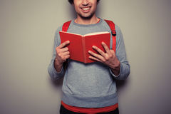 Happy young student with red book stock images