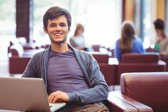Happy young student sitting on couch using laptop Stock Photos