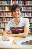 Happy young student sitting at desk reading a book Stock Photos