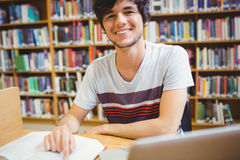 Happy young student sitting at desk reading a book Stock Photography