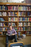 Happy young student sitting on library floor reading Royalty Free Stock Photos