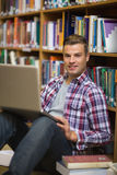 Happy young student sitting on library floor using laptop Royalty Free Stock Image