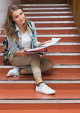 Happy young student sitting on stairs looking at camera Royalty Free Stock Photos