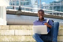 Happy young student sitting on steps with laptop. Portrait of happy young student sitting outdoors on steps with laptop and smiling Royalty Free Stock Photo