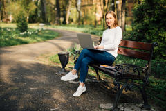 Happy young student with a tablet and a disposable coffee cup sitting on the bench and reading in a summer park. Stock Images
