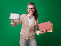 Happy student woman with books and tablet PC isolated on green. Happy young student woman with books and tablet PC isolated on green stock images
