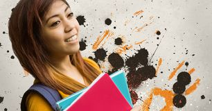 Happy young student woman holding notebooks against grey, yellow and black splattered background. Digital composite of Happy young student woman holding Royalty Free Stock Photography