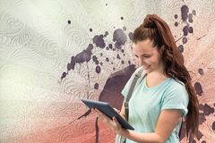 Happy young student woman holding a tablet against white, red and purple splattered background. Digital composite of Happy young student woman holding a tablet Royalty Free Stock Photography