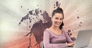 Happy young student woman using a computer against white, red and purple splattered background. Digital composite of Happy young student woman using a computer Stock Photos