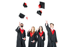Happy young students with diplomas throwing graduation caps isolated. On white Stock Photography