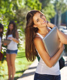 Happy young students outdoors in sunny day Stock Photo