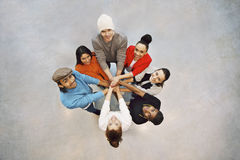 Happy young students showing unity as a team. Group of happy young students showing. Top view of multiethnic group of young people putting their hands together Stock Photography