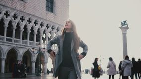 Happy young stylish European woman tourist enjoying walking along old antique San Marco city square in Venice, Italy. Successful happy businesswoman finding stock footage