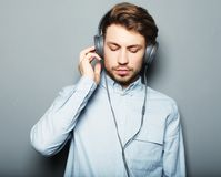 Happy young stylish man  adjusting his headphones ad smiling wh Royalty Free Stock Photo