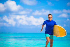 Happy young surf man runing at the beach with a Stock Photo
