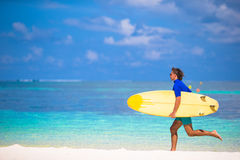 Happy young surf man runing at the beach with a Royalty Free Stock Photos