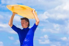 Happy young surf man at white beach with yellow. Strong young surf man runing at the beach with a surfboard Royalty Free Stock Images