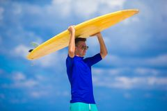 Happy young surf man at white beach with yellow. Strong young surf man runing at the beach with a surfboard Stock Photo