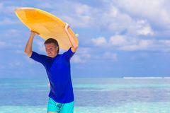 Happy young surf man at white beach with yellow Stock Photo