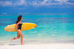 Happy young surf woman runing at the beach with a Royalty Free Stock Photos