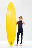 Happy young surfer holding surfboard and showing thumbs up. Gesture isolated on the white background Royalty Free Stock Photos
