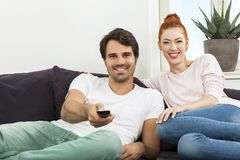 Happy Young Sweet Couple Sitting at the Couch Royalty Free Stock Photography