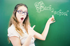 Happy young teacher or student pointing back to school. Successful happy young teacher or student is pointing at blackboard of text and concept of back to school Stock Image