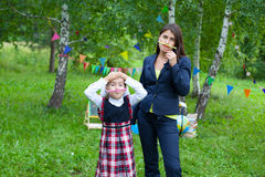 Happy young teacher woman mother and schoolgirl wearing uniform Royalty Free Stock Photos