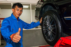 Happy young technician giving thumbs up while replacing tires.  Stock Photo