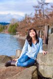 Happy young teen girl face upturned, smiling, while sitting outdoors on rocks along lake shore Royalty Free Stock Photography