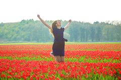 Happy young teen girl jumping up against a spring tulip field. Stock Photo