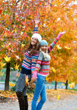 Happy young teen girls in autumn scenery. Throwing leaves Stock Photo