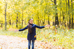Happy young teen girls in autumn scenery throwing leaves.  Stock Photos