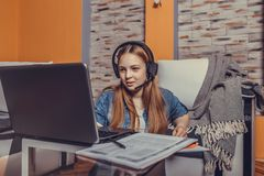 Cute teenage girl wearing headphones and  having a video conference online with a laptop stock photography