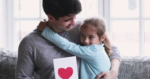 Cute small child girl congratulating smiling daddy with Father`s Day.