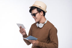 Happy young tourist asian man holding passport over grey backgro Royalty Free Stock Photo