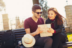 Happy young tourist couple sitting on the bench Royalty Free Stock Image