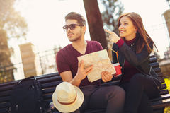 Happy young tourist couple sitting on the bench Stock Images