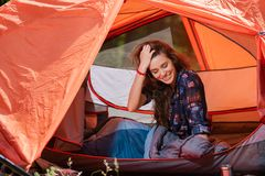 Happy young tourist girl smiling in tent. Happy young tourist girl smiling in red tent royalty free stock photos