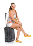 Happy young tourist woman sitting on wheel bag Royalty Free Stock Images