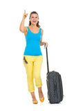 Happy young tourist woman with wheel bag pointing on copy space Royalty Free Stock Images