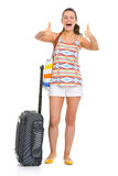 Tourist woman with wheel bag showing thumbs up Royalty Free Stock Photo