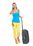 Happy young tourist woman with wheel bag showing thumbs up Stock Images