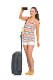 Happy young tourist woman with wheel bag taking photos Stock Images